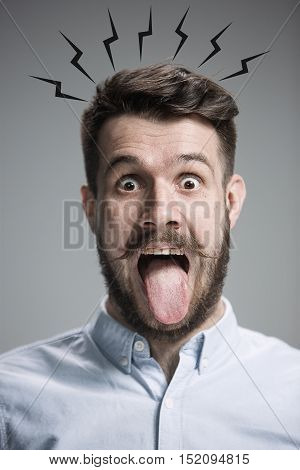 The tongue hanging out man on the gray background. concept of extreme mental stress