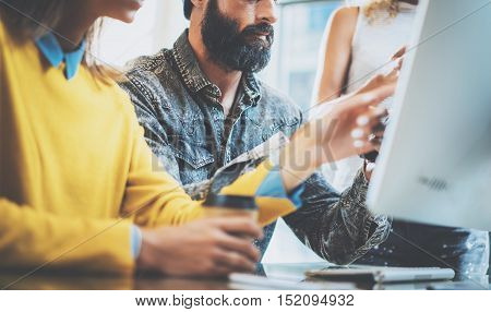 Bearded man working in the office with colleagues.Coworkers people discussing business ideas on a workplace.Horizontal, blurred