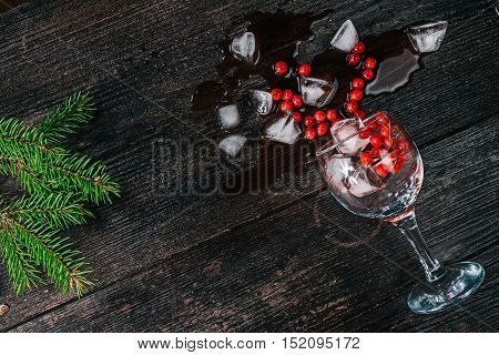 Wine glass with ice cubes and red berries lying on the dark wood surface decorated with fur tree twigs. Flat lay