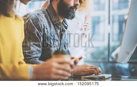 Bearded man typing on desktop keyboard in a office. Young coworkers discussing business ideas on a workplace.Horizontal, blurred
