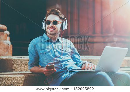 Full of gladness. Joyful content smiling young man using laptop and listening to music while resting on the footsteps