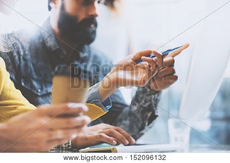 Bearded man and woman working together in modern office. Girl holding a pen in hand and pointing to computer screen.Horizontal, blurred background