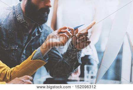 Closeup photo of bearded man and woman working together in modern office. Girl holding a pen in hand pointing to computer screen.Horizontal, blurred background