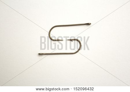 Two Fishing Hooks On A White Paper Background