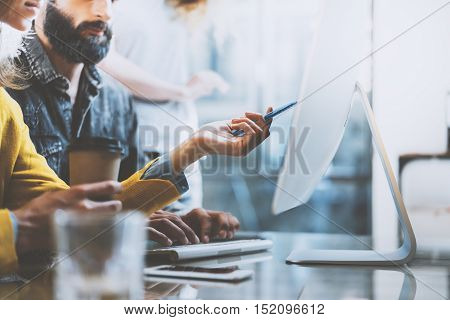 Photo of bearded man and woman working together in modern office. Girl holding a pen in hand and pointing to computer screen.Horizontal, blurred background