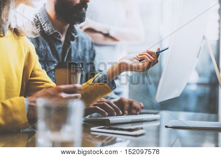 Group of young coworkers working together in a sunny office.Man typing on computer keyboard at wood table.Woman pointing hand to desktop screen.Horizontal photo , blurred