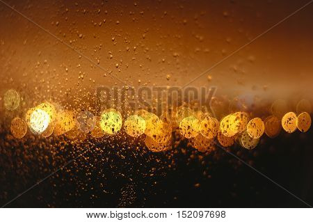 Yellow and Orange Bokeh on a dark background with drops on a window glass