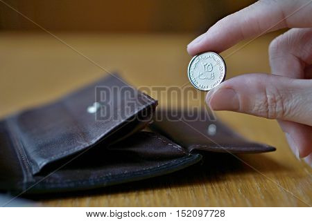 Male hand holding one coin from the United Arab Emirates (UAE dirham, AED) and withdrawing that from the brown leather wallet