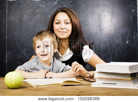 little cute boy with young teacher in classroom studying at blackboard smiling, doing homework