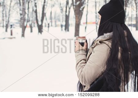 Rear view of young woman in beige jacket and black beanie hat, with log black hair, holding a cup of takeaway coffee. Outdoors, natural light, matte color filter applied, unrecognizable person.