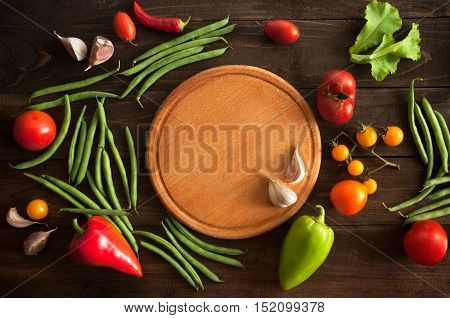 raw vegetables with cutting вoard on wooden background cooking