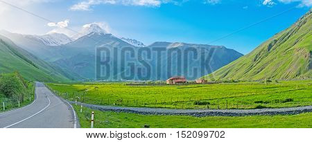 The green meadows of Sno valley with the sunset view on Kazbek Mount colored with the sun beams Kazbegi Georgia.