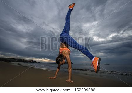 Girl standing upside down on the beach