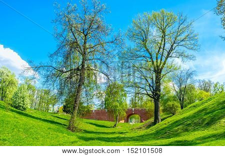The ravine covered with juicy grass with the view on Greenhouse Bridge between the Royal Greenhouses and Bread House Tsaritsyno Moscow Russia.