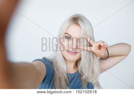 smiling young girl making selfie photo over white background. Blond swedish girl showing two fingers. Number 2