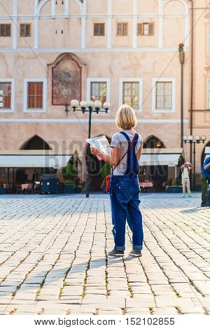 Woman looks at map in the old town square. Travel guide, tourism in Europe, female tourist with map. Kostel Panny Marie pred Tynem. Church of the Virgin Mary.