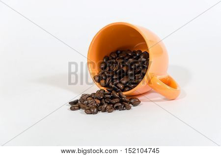 coffee beans in orange cup on a white surface