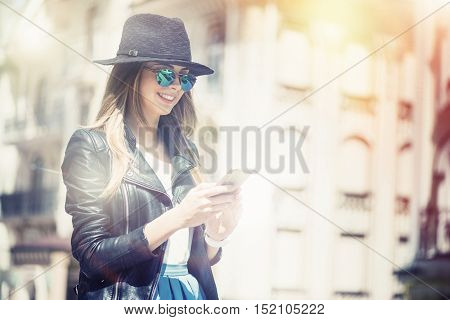 Full of positivity. Cheerful content smiling young woman using cell phone and expressing gladness while walking