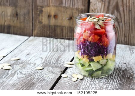 Healthy Homemade Mason Jar Salad With Cucumber, Cheese, Tomato, Red Cabbage And Pumpkin Seeds