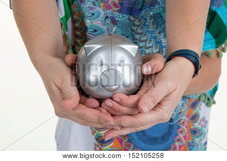 Mother and young girl holding piggy bank