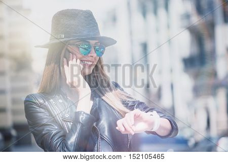 Trace your time. Cheerful delighted trendy young woman smiling and talkgin on cell phone while looking at her smart watch