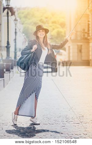 Share positivity. Cheerful charming smiling woman standing in the street and catching a taxi while having a walk