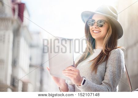 No step without technologies. Cheerful smiling elated young woman using tablet and expressing gladness while walking in the city