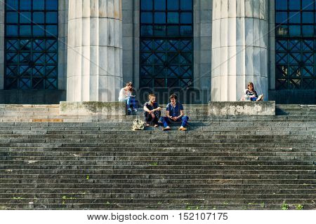 Two young men chatting and two other young women studying on the steps of the Law School of the University of Buenos Aires on the evening of October 11 2016