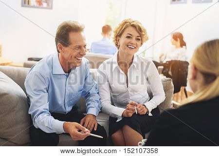 Joyful business team is resting in lounge office room and talking. They are sitting on sofa and smiling