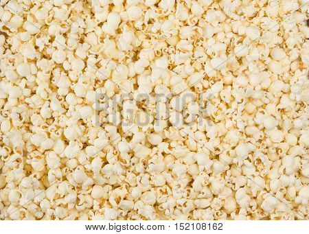 Scattered salted popcorn, food texture background. Fastfood popular during a movie in a cinema