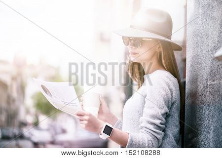 Daily press. Pleasant deligted charming woman reading newspaper and drinking coffee while resting outside