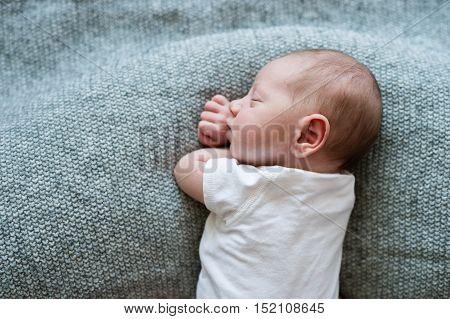 Cute little newborn baby boy lying on bed, sleeping, close up