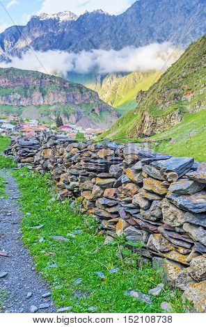 The stone fragments from the local mountains are the best materials for the fence Stepantsminda Kazbegi Georgia.