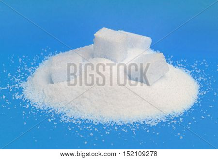 Close-up of pile of sugar isolated on blue background