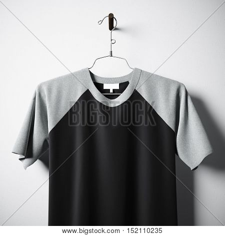 Closeup of blank cotton tshirt of black color hanging in center empty concrete wall. Clear label mockup with highly detailed textured materials. Square. Front side view. 3D rendering