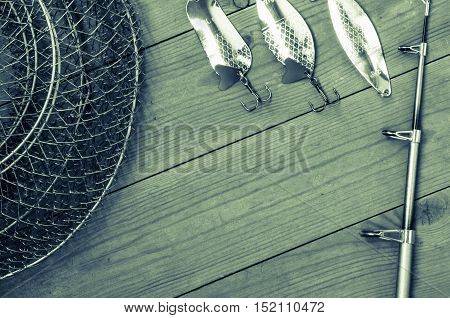 Fishing accessories for summer consisting of tackle, bait, hook. Wooden background. Outdoor activity and leisure concept. Toned.