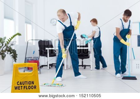 Cleaners during work mopping floor and dusting office interior