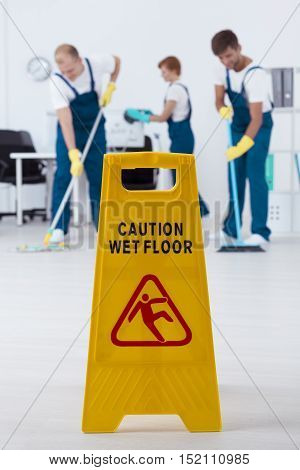 Shot of yellow wet floor sign and cleaners mopping floor