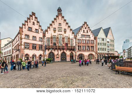 Frankfurt am Main Germany - May 23 2016: Tourists on the Romerberg Square on a cloudy rainy weather in Frankfurt am Main Germany Hesse Germany.
