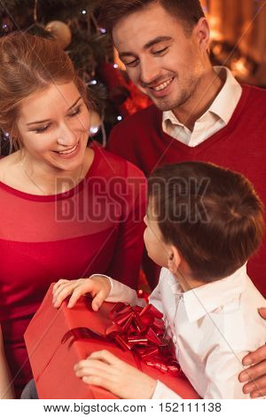 Little boy getting Christmas gift from parents