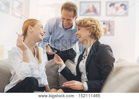 Happy colleagues are talking and laughing in lounge office room. Women are sitting on sofa with relaxation. Man is standing and looking at them with joy