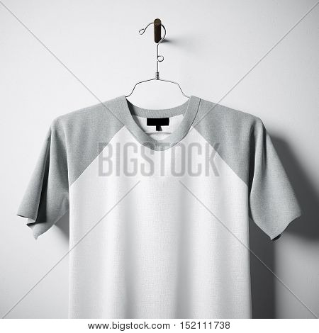 Closeup of blank white and gray cotton tshirt hanging in center of empty concrete wall. Clear label mockup with highly detailed textured materials. Square. Front side view. 3D rendering