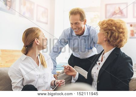Confident senior businessman is explaining his idea to colleagues. He is standing and smiling. Women are sitting and looking at him with interest