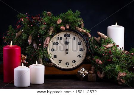 Happy New Year decoration. Vintage clock showing twelve. Candle and fir branch on woodtn background.