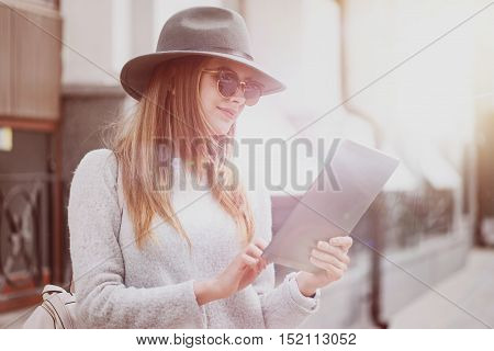 PImprove your mood. Joyful content young woman using tablet and standing in the street while having rest