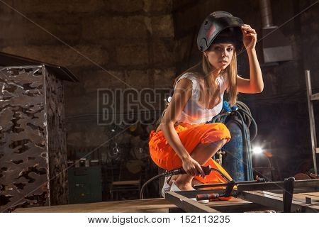 Blond Sexy Welder Woman In The Protective Mask Is Looking At The Camera.