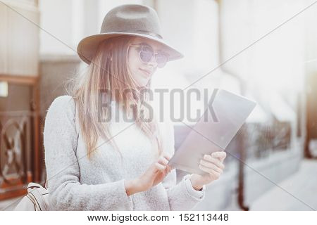 get rid of routine. Pleasant content woman smiling and using tablet while standing in the street