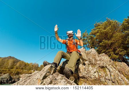 Successful young man, using virtual reality goggles to tour in the mountains, on vacation in the summer