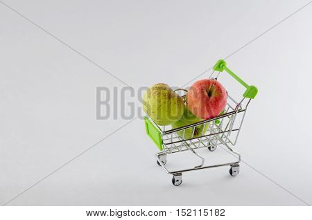 Fresh apple in the shopping cart. Fruit photo. Healthy product. Isolated. Raw food at supermarket.