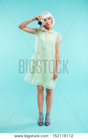 Full length of pretty young woman photographer standing and using photo camera